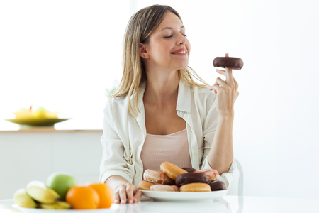 Shot of pretty young woman choosing between fruit and sweet, and finally, choose donuts at home.