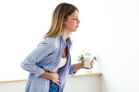 Shot of unhealthy young woman with stomachache holding a glass with milk at home. Stockfoto