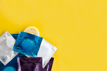 Close-up of multi colored condoms over yellow background.