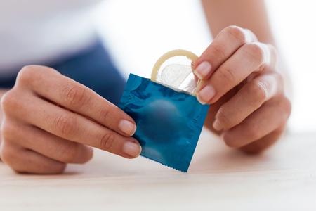Primo piano della giovane donna che tiene il preservativo pronto per l'uso per una cassaforte su sfondo bianco.