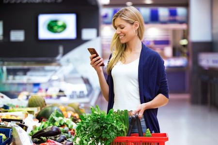 Foto de hermosa mujer joven mirando la lista de la compra en el teléfono móvil mientras compra verduras frescas en el mercado. Foto de archivo - 107452048