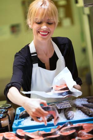 Portrait de jolie jeune vendeur choisissant une paix de saumon sur le marché.