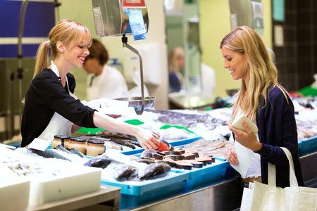 Plan d'une belle femme heureuse vendant du poisson frais au client sur le marché. Banque d'images
