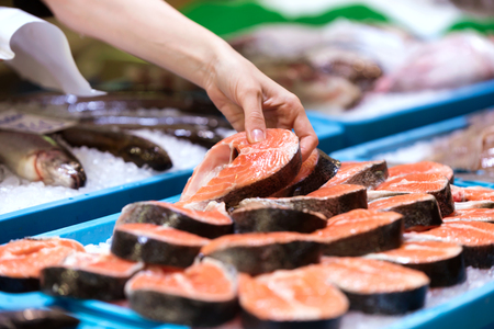 Close-up of young seller choosing a peace of salmon in the market. Stock Photo