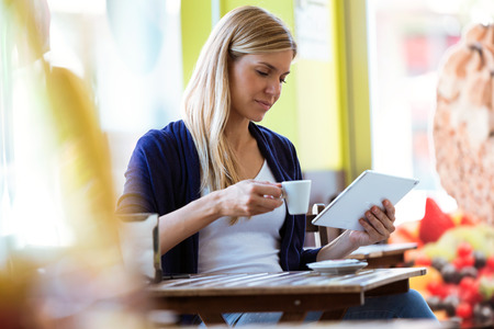 Shot of beautiful young woman using her digital tablet while drinking coffee in a coffee shop.