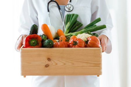 Close-up of nutritionist holding wooden box with fresh vegetables over white background. Stock Photo
