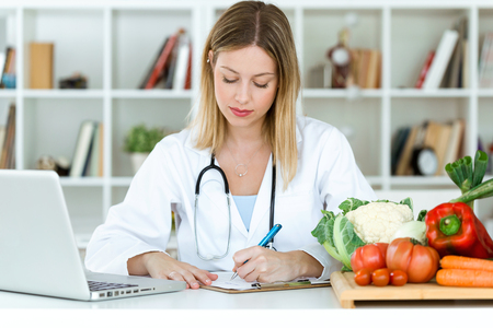 Shot of beautiful young nutritionist working at desk and writing medical records over fresh fruit in the consultation. Imagens