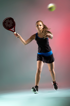 Shot of beautiful young woman playing padel indoor over multicolored background.