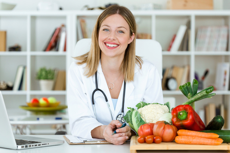 Portrait of beautiful smiling nutritionist looking at camera and showing healthy vegetables in the consultation.