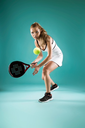 Shot of pretty young woman playing padel indoor over green-blue background.