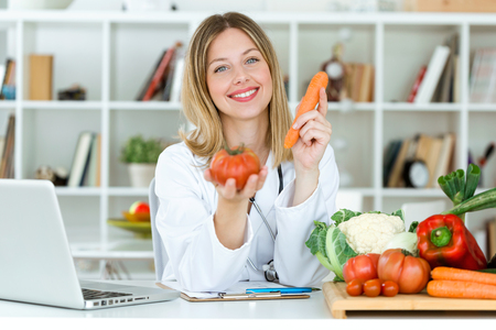 Portrait of beautiful young nutritionist looking at camera and holding fresh vegetables in the consultation.