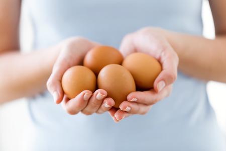 Nahaufnahme der jungen Frau, die braune Hühnereier über weißem Hintergrund hält.