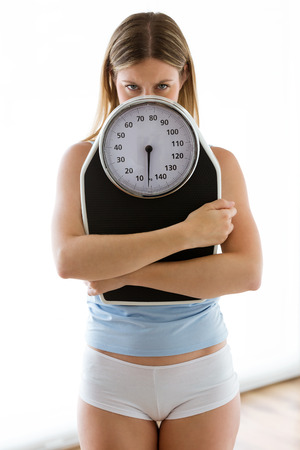 Portrait of frustrated young woman looking at camera with weigh scale over white background.