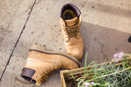 Close-up of brown dirty boots thrown to the ground in the greenhouse Stock Photo