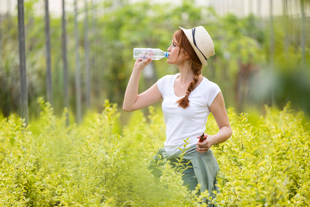 Shot of beautiful young woman drinking water bottle in the greenhouse