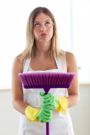 Portrait of boring young woman holding broom while cleaning at home. Archivio Fotografico