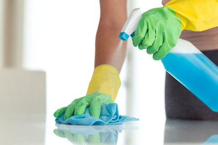 Close-up of young woman in protective gloves wiping dust using a spray and a cloth while cleaning her house 版權商用圖片
