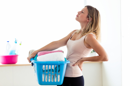 Shot of beautiful young tired woman with back pain holding basket with clean clothes at home.