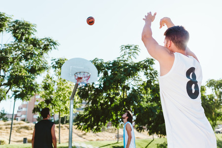 Outdoor portrait of group of friends playing basketball on court. 版權商用圖片