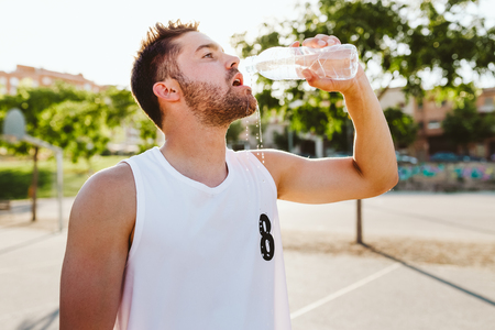 Outdoor portrait of handsome young man drinking water on court. Stock Photo