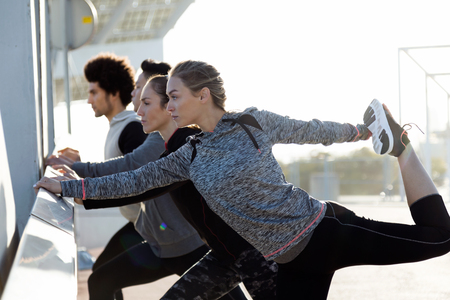 Outdoor portrait of running people doing stretching in the city. Stock fotó
