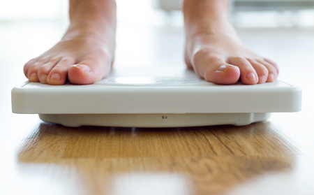 Portrait of young healthy girl on home scales. Stock Photo