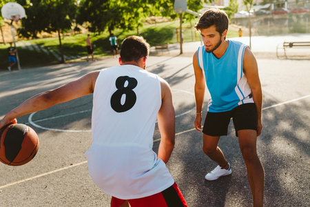 Outdoor portrait of two friends playing basketball on court.