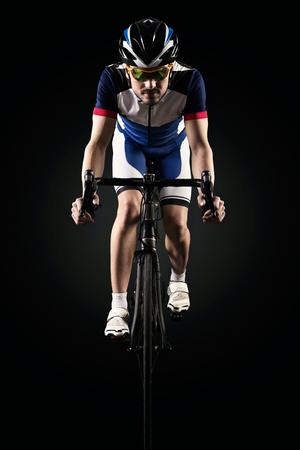Ritratto di bel giovane in bicicletta indoor. Isolato sul nero.