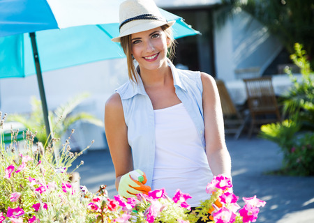 Portrait of beautiful young woman taking care of the garden house. Stockfoto