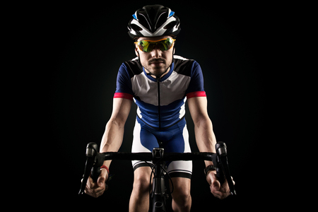 Portrait of handsome young man cycling indoor. Isolated on black. Stockfoto - 111521698