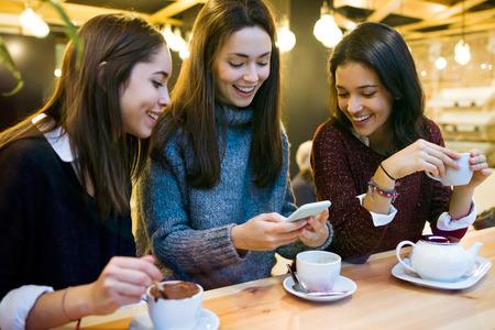 Portrait de trois belles jeunes femmes utilisant un téléphone portable au café.