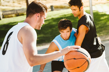Outdoor portrait of group of friends playing basketball on court. Stock Photo