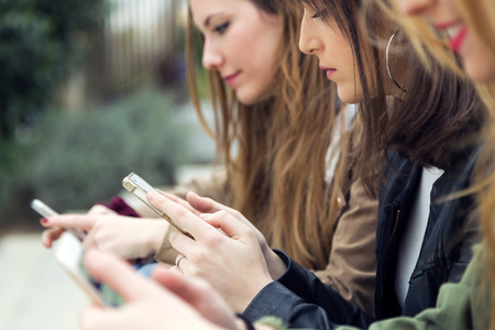 Portrait of three young women using a mobile phone in the street. Imagens