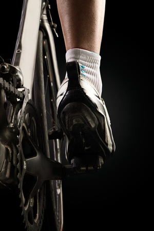 Close-up of the foot of a young man cycling. Isolated on black. Stockfoto - 111521961