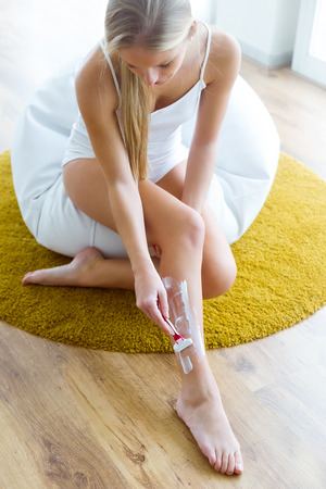Portrait of beautiful young woman shaving her atracctive legs.