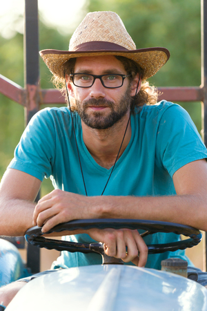 Portrait of young hipster farmer in tractor looking at the camera in the garden.