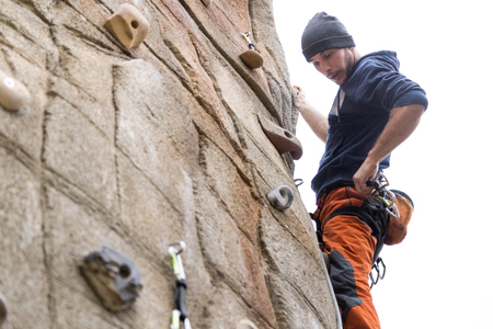 Portrait of handsome young man climbing natural rocky wall.