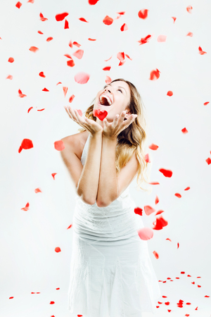 Portrait of beautiful young woman under a rain of rose petals. Isolated on white.