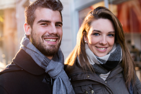 Portrait of beautiful young couple looking at camera in the street.