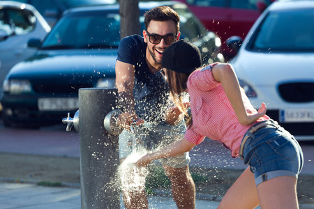 Outdoor portrait of two friends playing with a fountain in the street.
