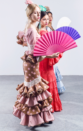 Portrait of pretty three young flamenco dancer in beautiful dress.