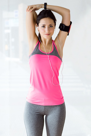 Portrait of beautiful sporty young woman doing exercise in gym.
