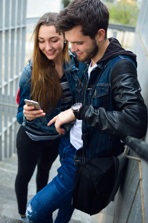 Portrait of two students using mobile phone in the street.