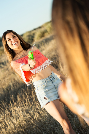 Portrait of beautiful young woman playing with water gun on field. Standard-Bild
