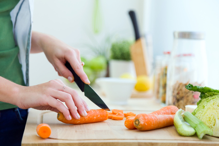 Portrait of pretty young woman cutting vegetables in the kitchen.