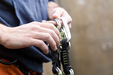 Portrait of young man preparing the equipment for climbing.