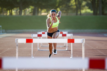 Portrait of young athlete jumping over a hurdle during training on race track.
