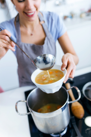Portrait of young woman serving vegetable soup in the kitchen.