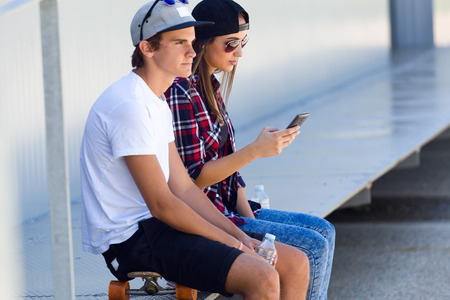 Portrait of two skaters using mobile phone in the street. 免版税图像