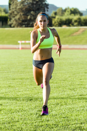 Portrait of fit young woman running on track field.